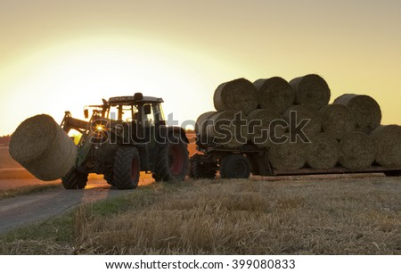 tractor at work on field bring haystacks home in sunset - stock photo