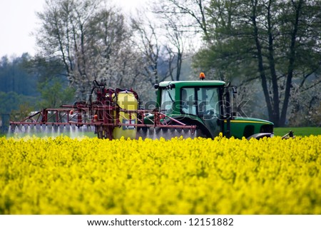 Tractor crop spraying with fertilizer onto field - stock photo