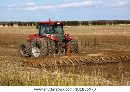 Tractor cultivated field in early spring - stock photo