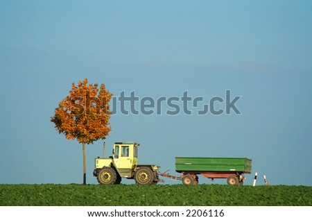tractor driving along field in autumn - stock photo