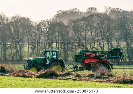 Tractor driving on a field with fertilizer in early spring - stock photo