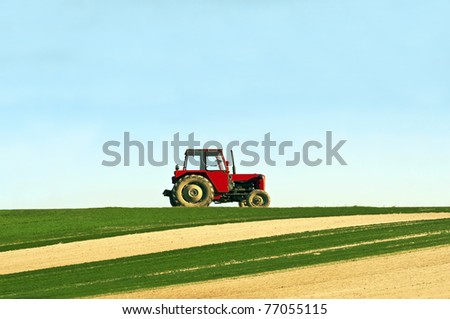 Tractor in a field - agricultural scene in summer - stock photo