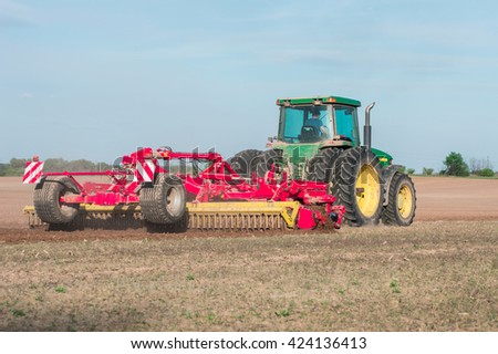 tractor in a field plowing land - stock photo