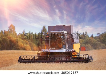 tractor in a field to harvest - stock photo