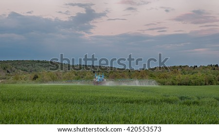 tractor in the agricultural field during the processing of Pesticides - stock photo