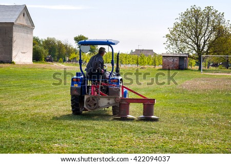 Tractor mowing the grass on the football field. - stock photo