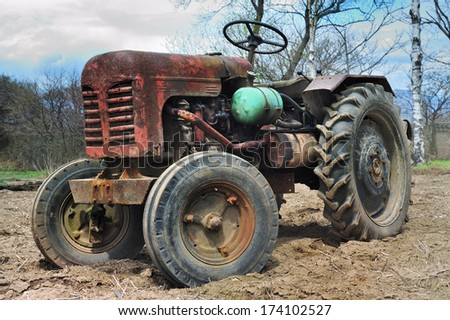 Tractor on an arable land close up - stock photo