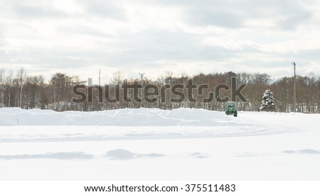 Tractor on cleaning snow Running track. - stock photo