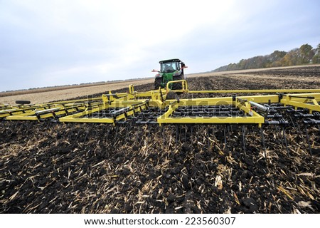 tractor on the field with wide-Tine Harrow - stock photo