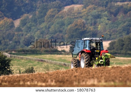 Tractor ploughing a field in rolling English landscape - stock photo