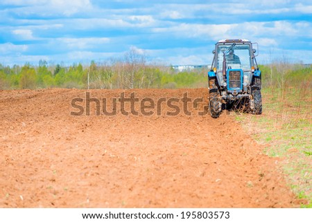 tractor plowed field in spring - stock photo
