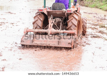 Tractor plowing the fields - stock photo