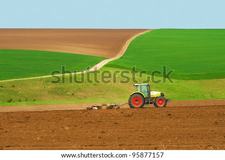 Tractor plowing the fields green with blue sky - stock photo