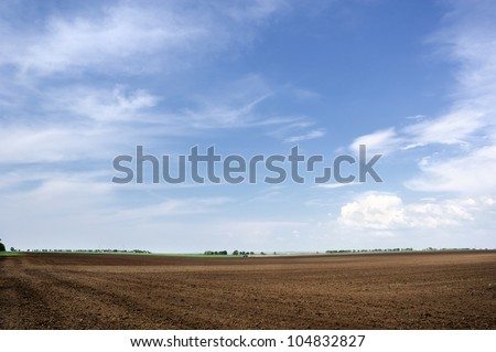 Tractor plowing the land. Arable land and sky. - stock photo