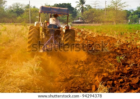 Tractor plows a field in Thailand - stock photo