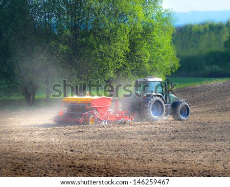 Tractor seeding grains in early spring - stock photo