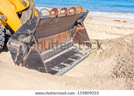 Tractor shovel on beach. Close up of heavy excavator loader bucket digging a trench in the sand. Blue ocean, waves rolling in background. Horizontal scene. - stock photo
