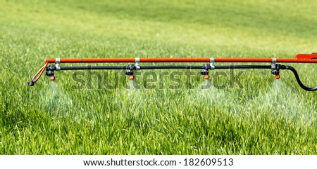Tractor sprayer spraying wheat in spring. - stock photo