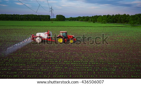 Tractor spraying field at spring,aerial view - stock photo