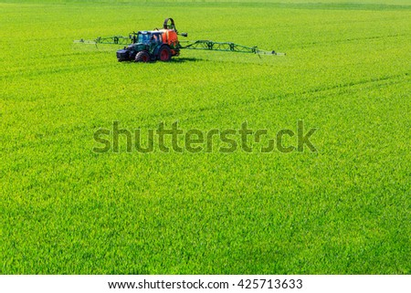 tractor spraying glyphosate pesticides on a field - stock photo