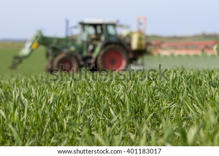 tractor spraying green field - agriculture background - stock photo