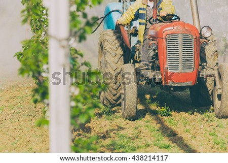 Tractor spraying on a cherry plantation. - stock photo