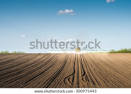 Tractor spraying on field - stock photo