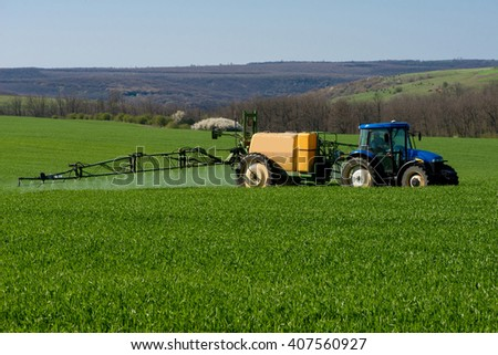 Tractor spraying pesticide in a field of wheat - copy space - stock photo