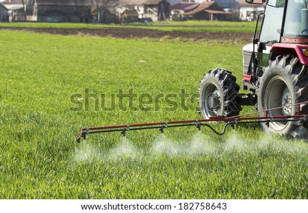 Tractor spraying wheat field with sprayer, pesticides and herbicides - stock photo