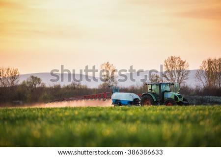 Tractor spraying wheat field with sprayer, sunsetshot - stock photo