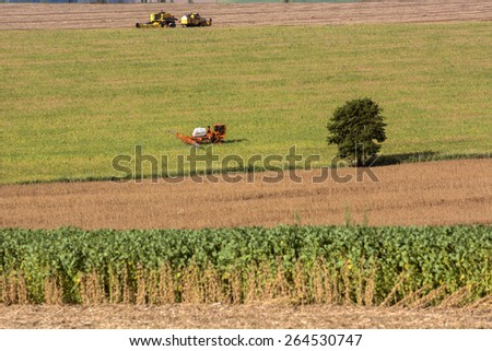 Tractor sprays which protect against pests at a farmer's field  - stock photo