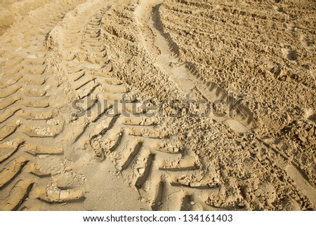 Tractor tire tracks on beach sand. - stock photo