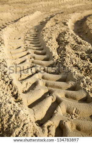 Tractor tire tracks on beach sand. Shallow depth of field. - stock photo