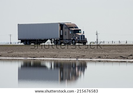 tractor trailer semi  truck driving on a highway causeway with reflection in water - stock photo