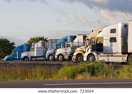 Tractor-trailer trucks in a line at a rest stop - stock photo