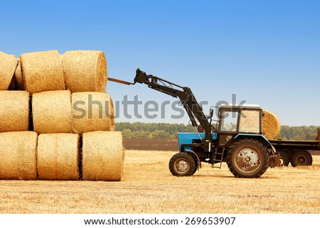 tractor unloads bales of hay in the field - stock photo