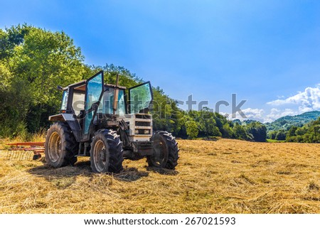 Tractor with open doors parked on dry grassland - stock photo