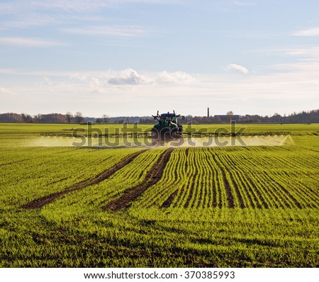 Tractor with sprayer on a wheat field. - stock photo