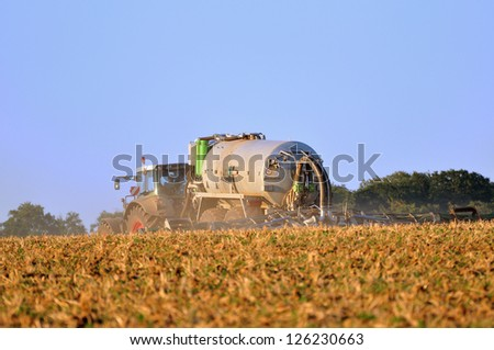 Tractor with sprayer working on field. - stock photo