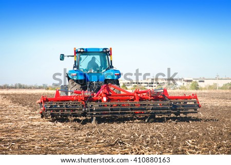 Tractor working in a field on a bright sunny day - stock photo
