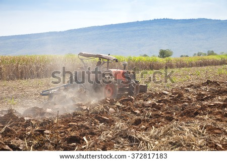 Tractor working in sugar cane field - stock photo