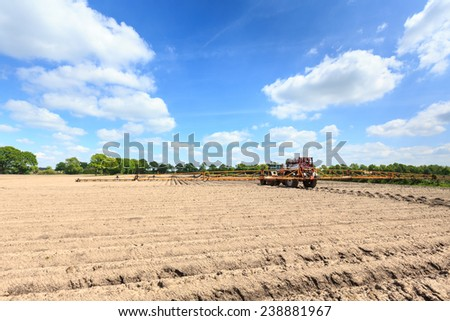 Tractor working on  a cultivated field in a countryside landscape in the Netherlands - stock photo