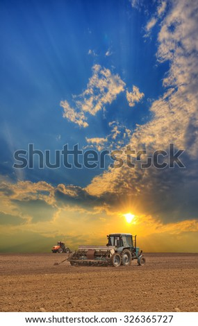 Tractors cultivating the field on sunset - stock photo