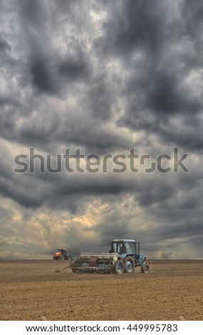 Tractors sowing the field with the seeder with dramatic sky on the background - stock photo