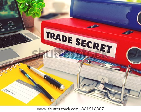Trade Secret - Red Office Folder on Background of Working Table with Stationery, Laptop and Reports. Business Concept on Blurred Background. Toned Image. - stock photo