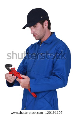 Tradesman adjusting a pipe wrench - stock photo