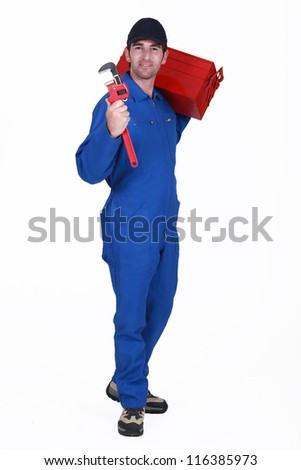 Tradesman carrying a toolbox and holding a pipe wrench - stock photo