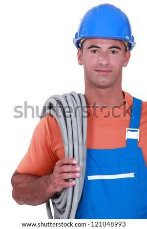 Tradesman carrying corrugated tubing around his shoulder - stock photo