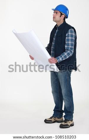 Tradesman examining a blueprint - stock photo