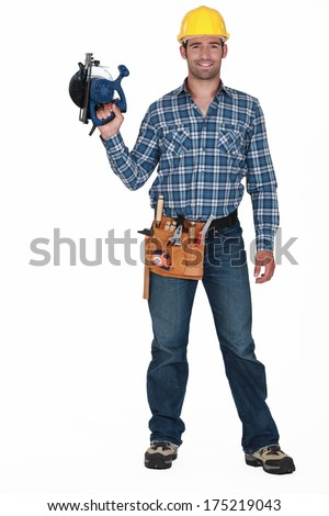 Tradesman holding a circular saw - stock photo